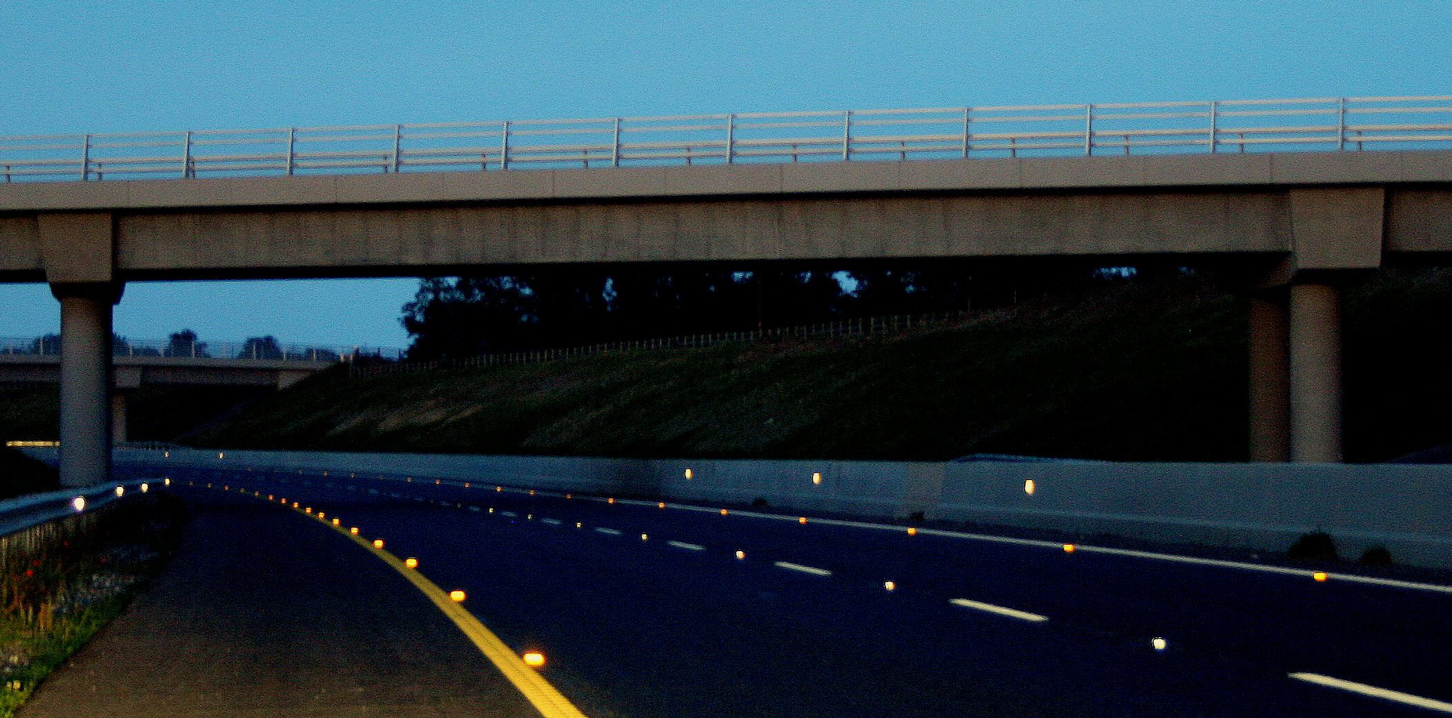 Photo of a motorway at night, with Catseyes reflecting the light of headlamps back at the vehicle it is coming from